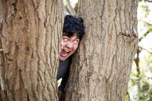 木の間から顔を出す男性