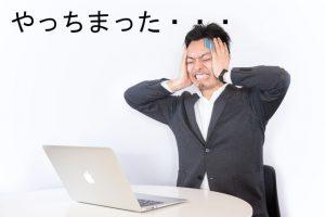 パソコンの前で己の失敗を嘆く男性